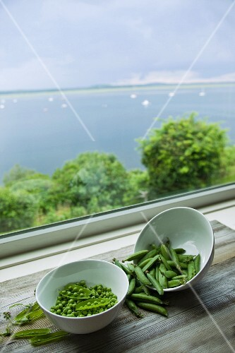 Peas and pea pods in bowls by a window with a sea view