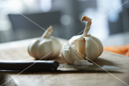 Bulbs of garlic with a knife on a chopping board