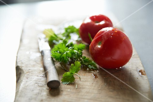 Fresh tomatoes and coriander on a chopping board with a knife