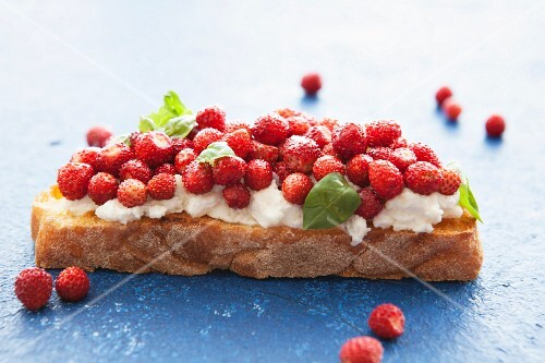 Bruschetta topped with ricotta, wild strawberries and basil