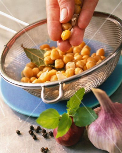 Cooked chickpeas with a bay leaf in a sieve