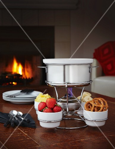 Chocolate fondue with strawberries, banana, pineapple and pretzels in front of a fire