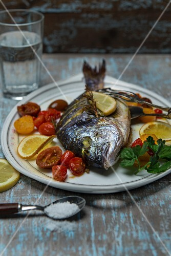 Roasted sea bream with grilled tomatoes, lemon, parsley, sea salt and rosemary