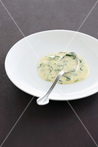 Bearnaise sauce with herbs on a plate with a spoon