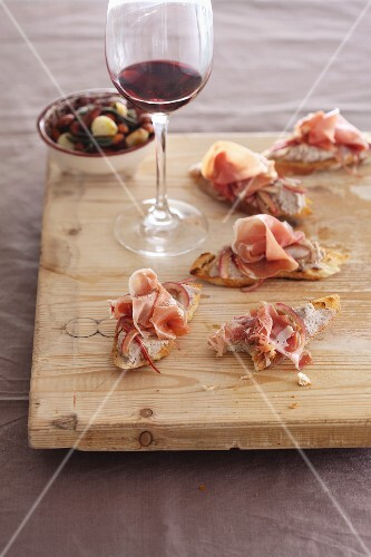 Crostini topped with borlotti bean purée and raw ham