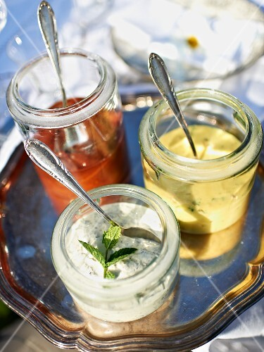 Assorted dips in glass jars with spoons