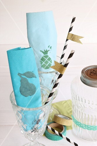 Paper napkins decorated with stamps, and straws decorated with masking tape flags