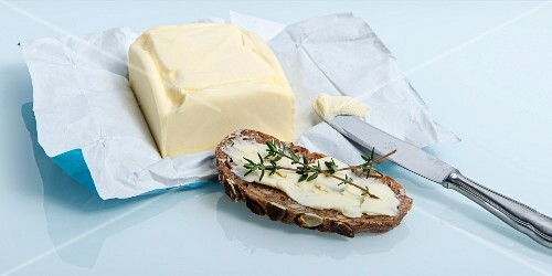 A slice of bread spread with butter and thyme