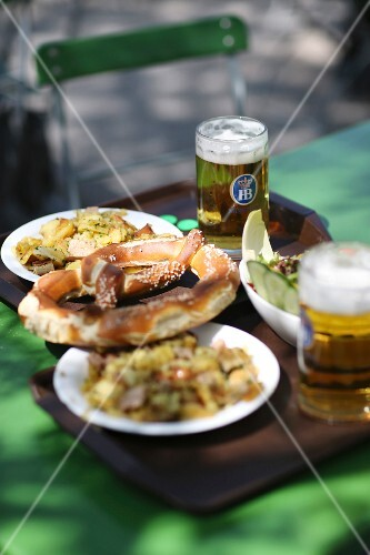 Supper and glasses of beer on a tray on a table in a beer garden (Germany)