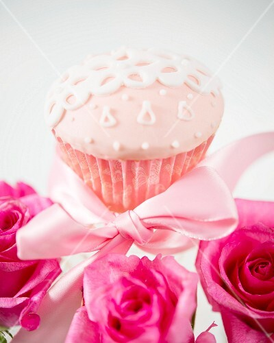A pink cupcake with sugar decorations