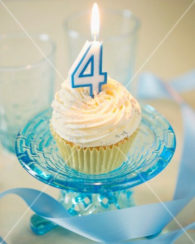 A vanilla cupcake for a 4th birthday with a burning candle