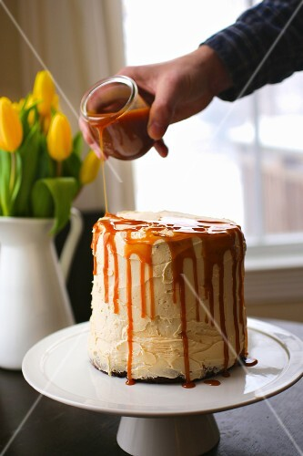 Caramel sauce being poured over a caramel cake