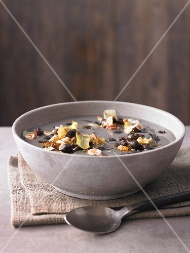 Chickpea soup with black chickpeas, fried white cabbage and roasted hazelnuts