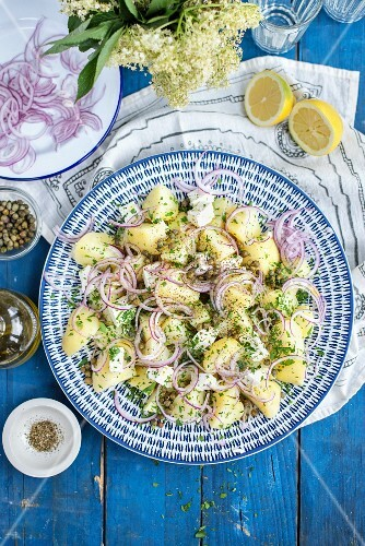 Greek potato salad with capers, onions, feta cheese and olive oil