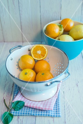 Oranges in an enamel colanders, oranges and lemons in a porcelain bowl with fresh mint