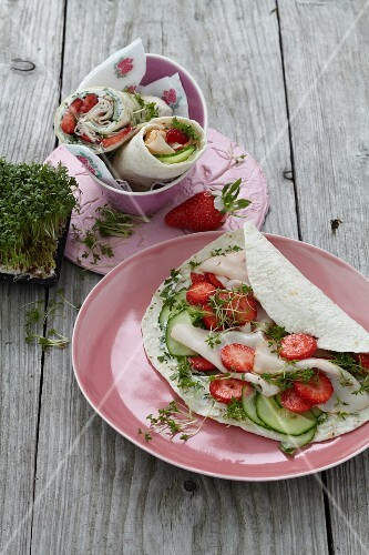 A chicken wrap with strawberries and cress