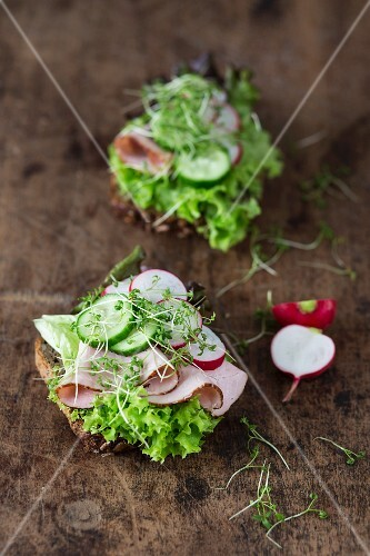 Two open sandwiches with lettuce, ham, cucumber and radishes on a wooden surface