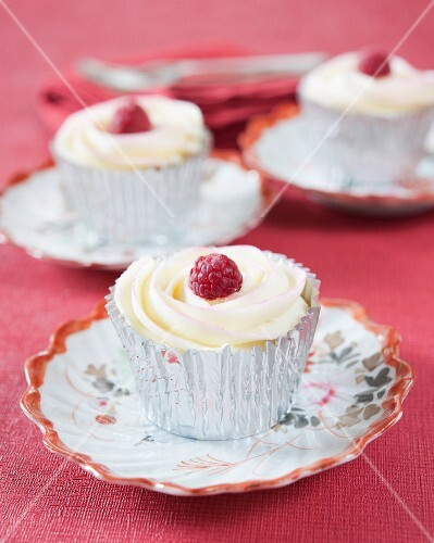 Cupcakes decorated with white chocolate and raspberries