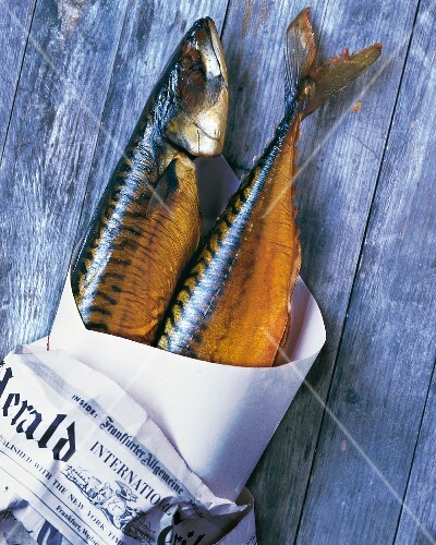 Two smoked mackerel in newspaper