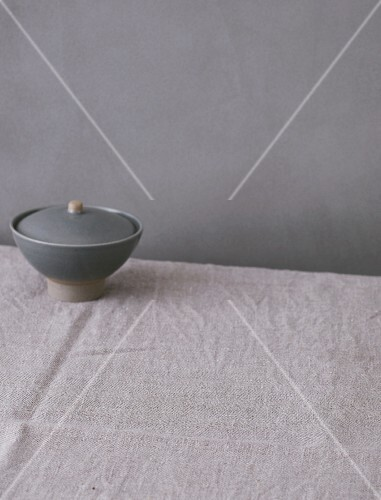 A linen cloth and a grey ceramic bowl on a grey surface