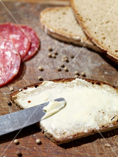 A slice of rye bread spread with butter with salami and peppercorns