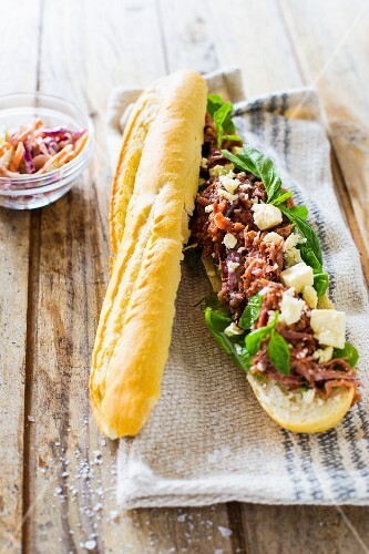A pulled pork baguette with mustard sauce, basil and feta cheese