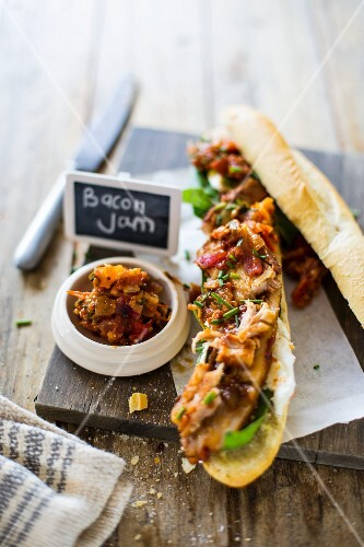 A baguette sandwich with roast pork fillet, bacon chutney, basil, mozzarella and chives