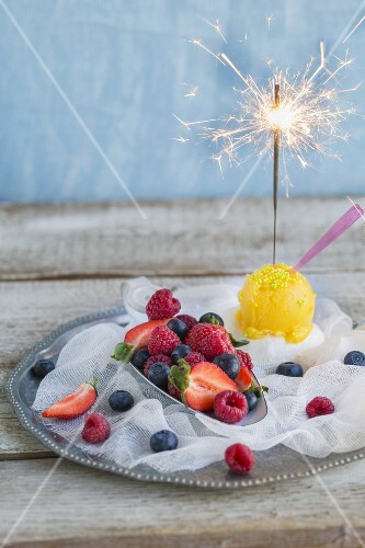 Mango sorbet with a sparkler and fresh raspberries, blueberries and strawberries
