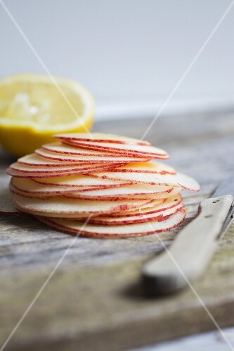 A stack of fine apple slices with a knife and a lemon