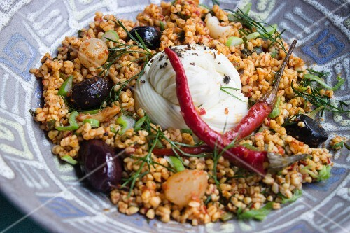 Bulgur salad with mozzarella, olives, chilli peppers and herbs