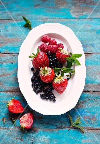 Fresh berries with mint leaves on a plate (seen from above)
