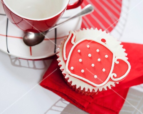 A cupcake decorated with a teapot