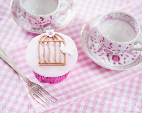 A cupcake decorated with a dove and a cage