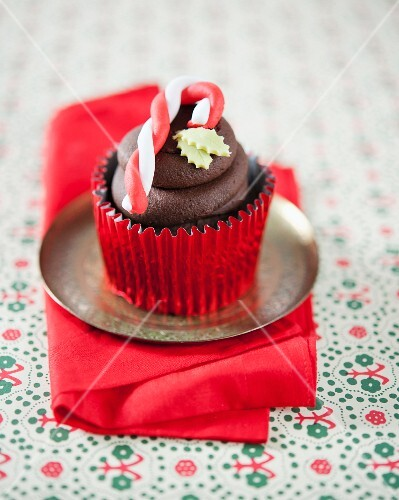 A chocolate cupcake decorated with a candy cane