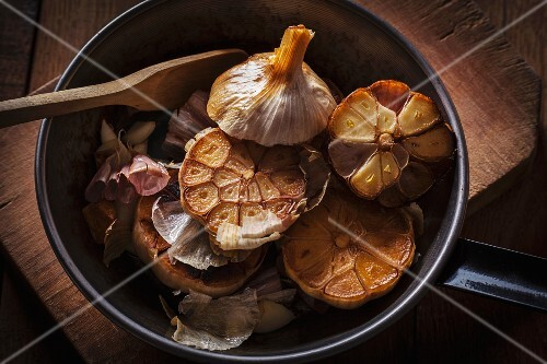 Halved, roasted garlic bulbs in a pan