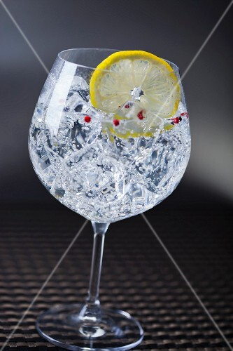 A gin and tonic with pink pepper and a slice of lemon