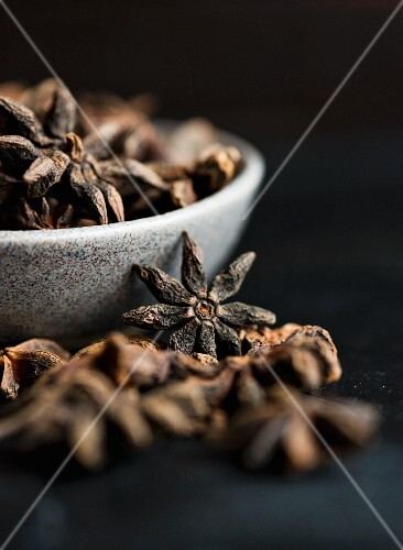 Star anise in and next to bowls (close-up)