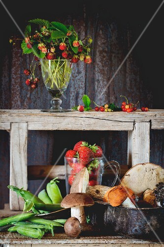 Wild mushrooms, young peas and strawberries on an old wooden table