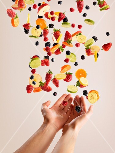 A girl's hands catching fruits and berries