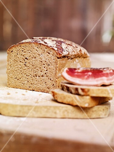 Sliced rye bread and a slice of ham on a wooden board