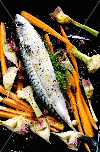Mackerel with carrots and artichokes on a baking tray