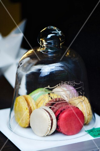 Colourful macaroons under a glass cloche