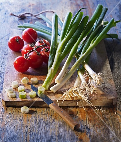 An arrangement of vine tomatoes and spring onions