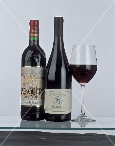 Bottle of Ribeira del Duero & of Barolo beside red wine glass