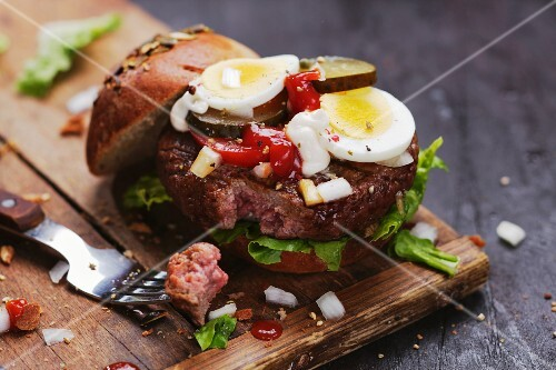 Beef tatar burger with egg, onions, ketchup and gherkins