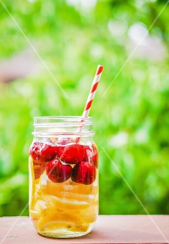 Fruity iced tea in a screw-top jar with a straw on a garden table
