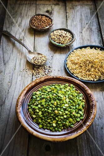 Split peas, brown rice, quinoa and buckwheat on a wooden surface