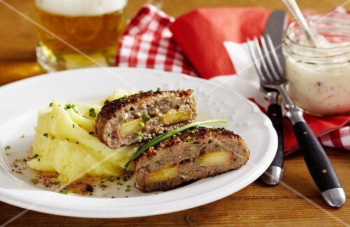 Minced meat steaks made with Appenzeller cheese and filled with apple served with mashed potatoes