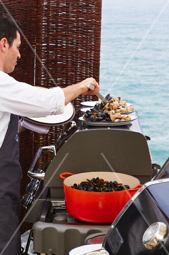 A cook serving mussels at a wedding by the sea