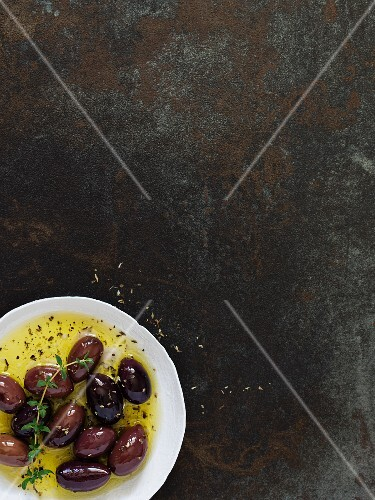 Marinated olives on rustic surface (seen from above)